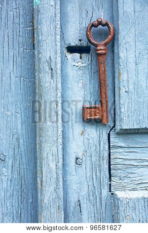 Old key on wooden antique door close-up