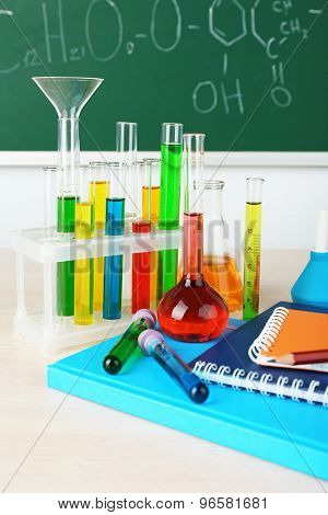 Desk in chemistry class with test tubes on green blackboard background
