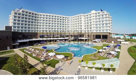 RUSSIA, SOCHI - JUL 25, 2014: People swim in pool of hotel Radisson Blu at summer sunny day. Aerial view. Photo with noise from action camera.