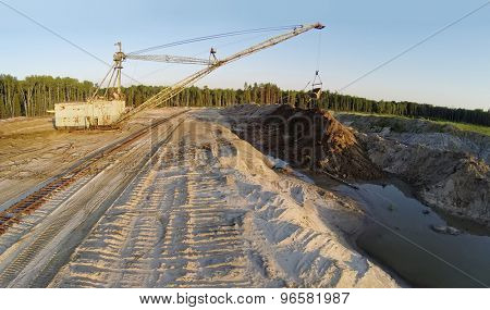 RUSSIA, VOSKRESENSK - JUL 1, 2014: Excavator works at sandpit during sunset. Aerial view. Photo with noise from action camera.
