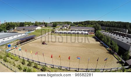 RUSSIA, MOSCOW - JUL 13, 2014: Tractor prepares sand on equestrian arena of sports complex Sozidatel before Russian Championship for Dzhigitovka. Aerial view. Photo with noise from action camera.