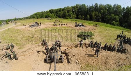 RUSSIA, MOSCOW - JUL 12, 2014: Soldiers in uniform of World War II stand near guns on battle field at spring sunny day. Aerial view. Photo with noise from action camera.