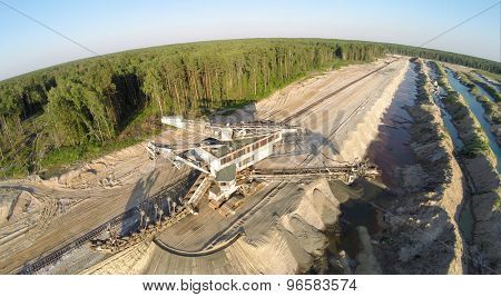 RUSSIA, VOSKRESENSK - 1 JUL, 2014: Spoker Takraf ERs 710 at sandpit near forest during sunset. Aerial view. Photo with noise from action camera.