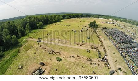 RUSSIA, NELIDOVO - JUL 12, 2014: Filed with soldiers formation and tribune with spectators during reconstruction Battlefield at sunny summer day. Aerial view. Photo with noise from action camera