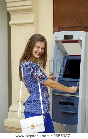 Smiling young woman in a blue blouse withdrawing money from ATM
