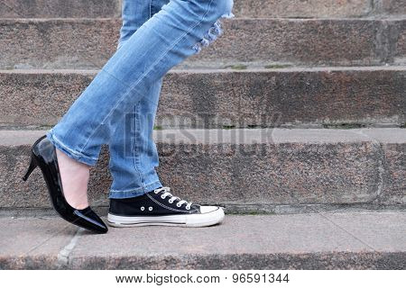 Female feet in different shoes on  stone stairs