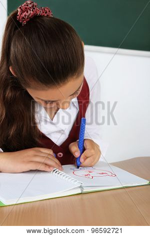 Beautiful little schoolgirl in classroom and draws in notebook