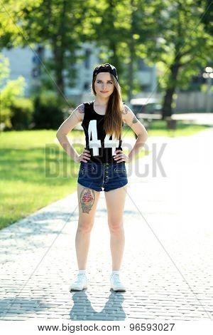 Beautiful girl with stylish make-up and tattooed body outdoors