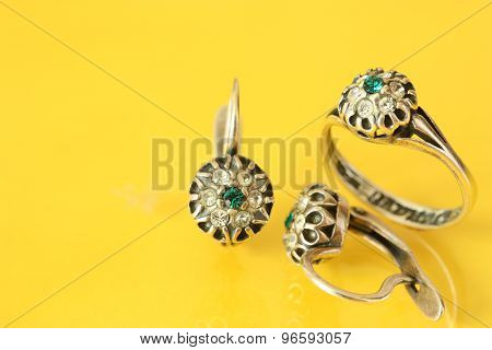 Women's earrings and a ring of white metal and green stones