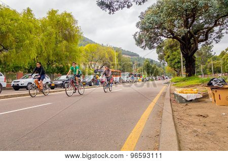 Unidentified hispanic cyclists moving through vehicle free street with heavy traffic in opposite lan