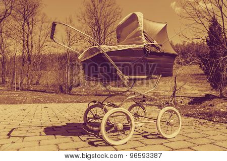 Retro style baby carriage outdoors on sunny day, sepia filter