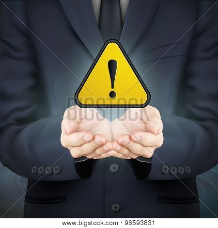 Businessman Holding Yellow Warning Sign