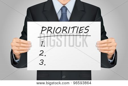 Businessman Holding Priorities Word Poster