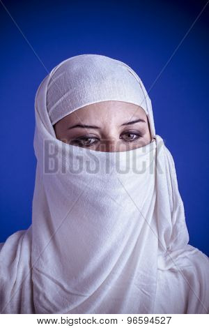 Beautiful arabic woman with traditional veil on her face, intense look