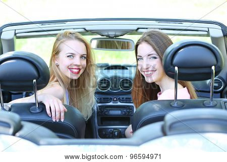 Two girls in cabriolet, outdoors