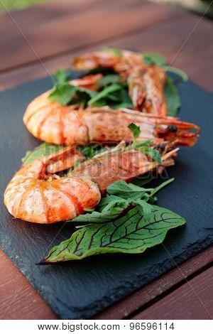 Grilled shrimps on slate plate, outdoor shot