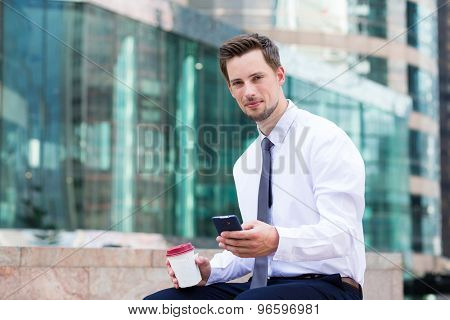 Young Businessman sitting with coffee and smartphone at Hong Kong
