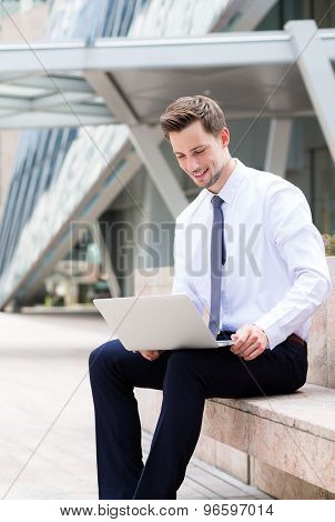 Caucasian young businessman sitting outside at hong kong