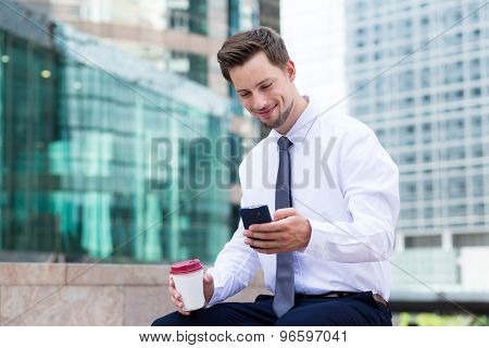 Caucasian young businessman with coffee and mobile phone at hong kong