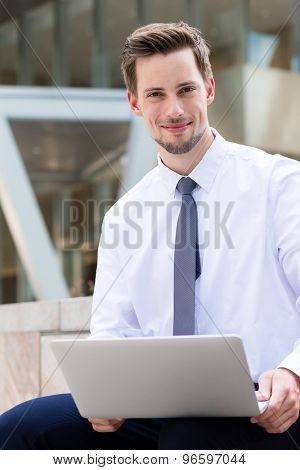 Businessman using the laptop computer at outdoor