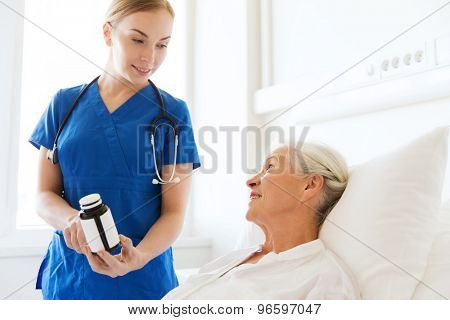 medicine, age, health care and people concept - doctor or nurse showing medicine to senior woman at hospital ward