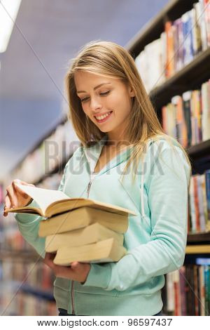 people, knowledge, education and school concept - happy student girl or young woman with book in library