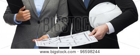 business, architecture and development concept - businesswoman and businessman with clipboard, bluepring and white helmet