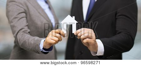 business, eco, real estate and office concept - businessman and businesswoman holding white paper house in office