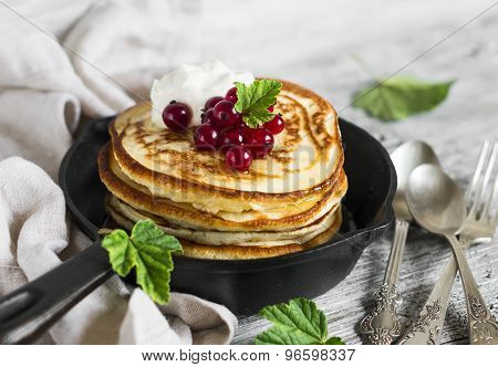 Pancakes With Honey, Sour Cream And Red Currants In A Vintage Scourage On A Light Wooden Background