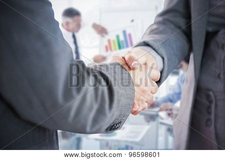 Business people shaking hands close up against business man giving a presentation