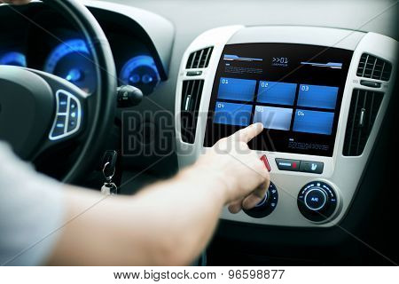 transport, modern technology and people concept - male hand pushing button on car control panel screen
