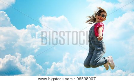 summer, childhood, leisure and people concept - happy little girl jumping high over blue sky and clouds background