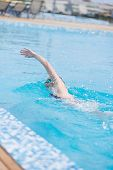 picture of crawl  - Young girl in goggles and cap swimming front crawl stroke style in the blue water pool - JPG