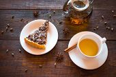 image of teapot  - The slice of vegetarian nut pie on a white plate lies on a dark wooden background - JPG