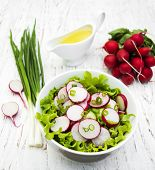 stock photo of radish  - Spring salad with cucumbers and radish on a wooden background - JPG