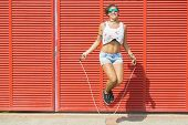 stock photo of jump rope  - Happy woman jumping rope on red background - JPG
