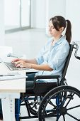 picture of independent woman  - Young disabled business woman in wheelchair working at office desk and typing on a laptop accessibility and independence concept - JPG