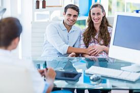 stock photo of gynecological exam  - Pregnant woman and her husband smiling at camera in an examination room - JPG