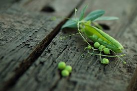 stock photo of pea  - open green peas on old wood, beads peas on wood, colored balls, pea pod ** Note: Shallow depth of field - JPG