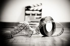 foto of clapper board  - 35 mm cinema film reel and out of focus movie clapper board in background on wooden floor in vintage black and white - JPG