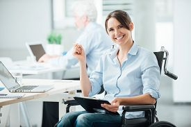 picture of wheelchair  - Happy female office worker in wheelchair holding a clipboard and smiling at camera disabled people support at workplace - JPG