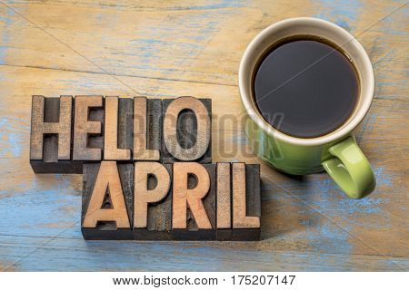 Hello April word abstract in vintage letterpress wood type with a cup of coffee