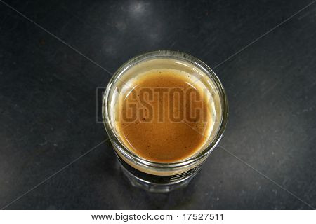 Espresso shot viewed from above on an aluminum table