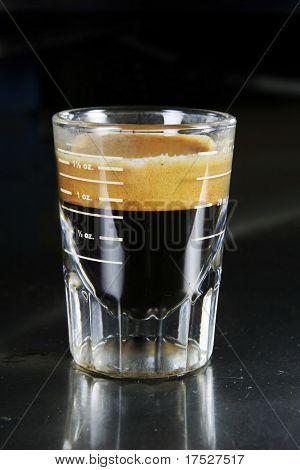 Single espresso in a shot glass with full crema