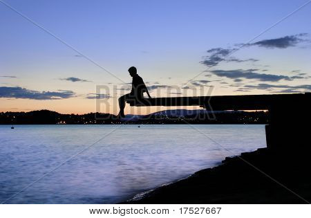 A young person sitting on a dock at dusk, at the fjord in Oslo, Norway