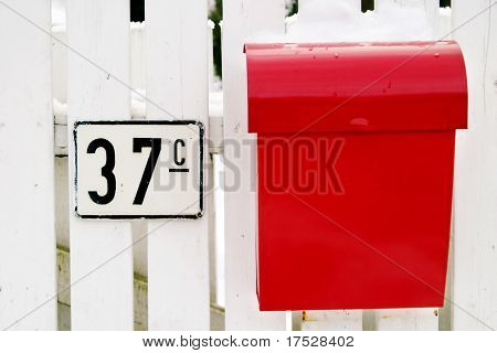 A retro mail box hanging on a white picket fence in Oslo Norway
