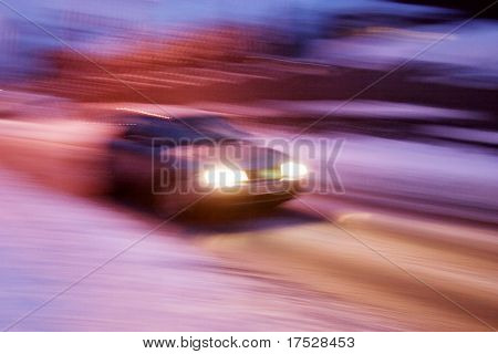 A abstract blur image of a car travelling at night.