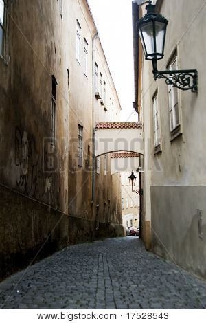 A dark moody image of a small skinny street in the old town area of Prague, Czech Republic.