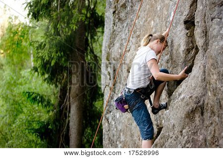 A female climber, climbing using a top rope on a steep rock face (crag)