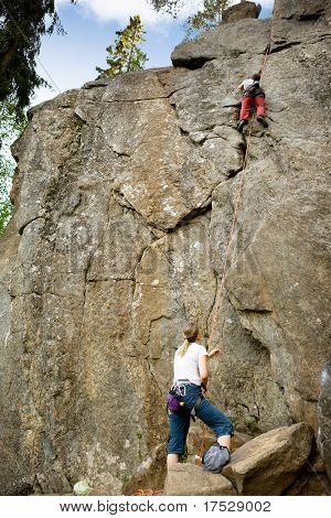 A female belaying a male on a steep rock face.